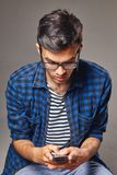Portrait of modern young man with mobile phone in a studio. Indoor portrait of modern young man with mobile phone Stock Photo