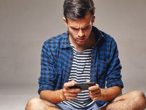 Portrait of modern young man with mobile phone in a studio. Indoor portrait of modern young man with mobile phone Stock Photos