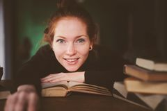 Indoor portrait of redhead happy student woman learning or reading books Royalty Free Stock Photos