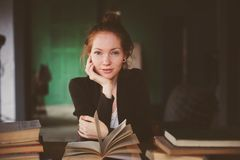 Indoor portrait of redhead happy student woman learning or reading books. Indoor portrait of redhead happy woman learning or reading books in university or royalty free stock images