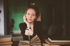 Indoor portrait of redhead happy woman learning or reading books in university. Or library Royalty Free Stock Photography