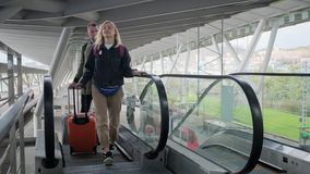 Traveling couple on airport escalator with baggage. Indoor portrait shot of a young lovely couple in stylish clothes all prepared for a vacation trip. Boyfriend stock footage
