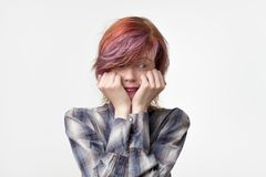 Indoor portrait of shy pretty female looking embarrassed wanting to say something, but not having courage to do it. She has interesting colored hairstyle Royalty Free Stock Photography