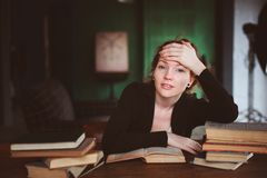 Indoor portrait of thoughtful or sad redhead woman learning or reading books. In university or library Royalty Free Stock Photo