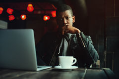 Indoor portrait of young black man sitting in cafe, drinking coffee or tea and working with lap top. Model looking at Stock Photo