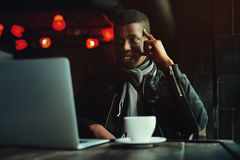 Indoor portrait of young black man sitting in cafe, drinking coffee or tea and working on lap top. Model looking at Stock Image