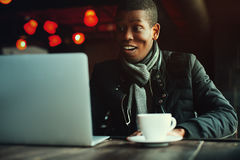 Indoor portrait of young black man sitting in cafe, drinking coffee or tea and working with lap top. Model looking at Royalty Free Stock Photos