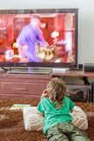 Indoor portrait of young boy watching tv. At home Stock Image