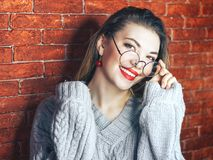 Indoor portrait of young good-looking girl in round glasses on red brick background with brown hair, laughing openly, expressing h. Picture of charming young Stock Photos