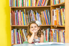 Indoor portrait of young happy smiling girl reading book in libr Royalty Free Stock Images