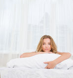 Indoor portrait of young woman sleeping or awaken in b Stock Image