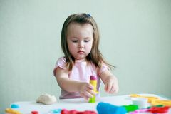 Indoor portrait of young 2 years happy smiling caucasian child girl playing with play dough royalty free stock images