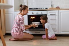 Indoor profile shot of smiling taking baking out of oven, her daughter standing near by and smelling delicious sweets, kid heping
