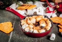 Indoor s'mores, baked s'mores dip. Indoor s'mores, baked s'mores dip in a cast iron skillet pan with graham crackers., dark grey table, copy Stock Image