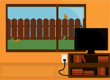Indoor scene. Orange room with a flatscreen tv on a bookshelf in front of a large window looking out into a green backyard with a wooden fence Royalty Free Stock Photos