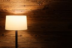 Indoor scene of a floor lamp against wooden wall stock photo