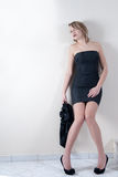 Indoor shoot of a model in a black dress. Indoor shoot of a blonde teen model with nice long legs in a short black dress holding a sweater, ready for nightlife stock photo