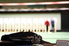 Indoor shooting range. Revolver with bullets on table in indor shooting range stock photos