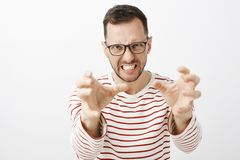Indoor shot of angry off european guy in black glasses, pulling hands towards camera and grimacing from outrage. Wanting to choke person who he hates, standing stock photos