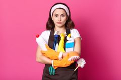 Indoor shot of attractive Caucasian young woman in white casual t shirt, and brown apron, holds cleaning detergents. Lazy girl royalty free stock photo