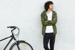Indoor shot of attractive man keeps hands crossed, looks thoughtfully, dressed in fashionable clothes, stands near bicycle, royalty free stock photo