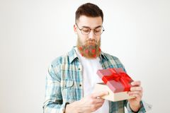 Indoor shot of bearded male model with long thick beard dressed in checkered shirt, opens present box, recieves surprise. From girlfriend, isolated over white stock images