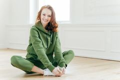 Indoor shot of beautiful redhead European woman has rest after cardio training, keeps legs crossed, dressed in green tracksuit,. Sits on floor alone. Healthy stock photos