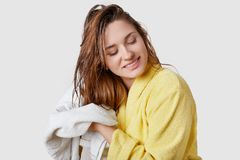 Indoor shot of beautiful woman wipes wet hair with towel, dressed in yellow bathrobe, stands against white background, has pleased stock photos