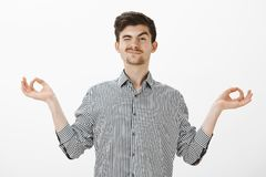 Indoor shot of carefree good-looking friendly guy with moustache in shirt, spread hands in zen gesture, peeking with one. Eye and smiling while watching Royalty Free Stock Photos