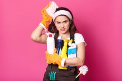 Indoor shot of Caucasian young woman with unpleasent facial expressoins, holds cleaning detergent, keeps hand with sponge in hand stock image