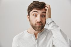 Indoor shot of clueless and puzzled attractive guy with messy beard, scratching head and looking with lifted eyebrows at royalty free stock images