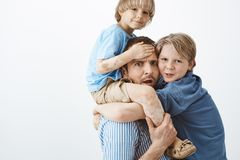 Indoor shot of concerned tired father holding cute blond son with vitiligo on shoulders, frowning and feeling worried. While older brother hanging on dad chest Royalty Free Stock Photo