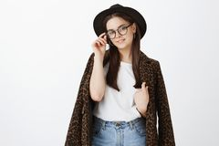 Indoor shot of confident beautiful and stylish feminine girlfriend in glasses, trendy hat and coat with leopard print. Touching rim of eyewear and smiling royalty free stock photos