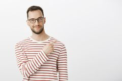 Indoor shot of confident pleased european man with bristle in black eyewear, smirking and pointing at upper right corner. Suggesting great way of solving Royalty Free Stock Photography