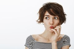 Indoor shot of curious emotive young female student with cute messy hairstyle, folding lips and saying wow while holding. Hand near mouth, looking left with stock photo