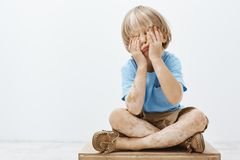 Indoor shot of cute european child with lovely haircut and vitiligo, covering face with palms while sitting, playing. Hide and seek with older brother, having royalty free stock photos
