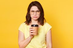 Indoor shot of dark haired girl with upset expression, purses lower lip, holds cup of coffee, wears round glasses, casual t shirt royalty free stock images