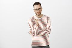 Indoor shot of determined creative businessman in black glasses and striped shirt, pointing at camera with index finger royalty free stock images