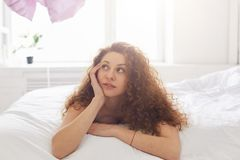 Indoor shot of dreamy woman with frizzy hair lies on bed with pe. Nsive expression, spends free time at bedroom, ponders about her plans for day. Beautiful Royalty Free Stock Photos