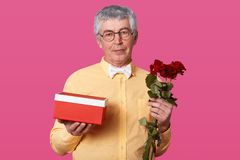 Indoor shot of elderly gentleman with serious facial expression holds gift box and red roses, dressed in yellow shirt with bowtie stock image