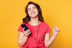 Indoor shot of enjoyable attractive woman smiling sincerely, dancing with raised hand and smartphone in her hand, having clenched royalty free stock photography