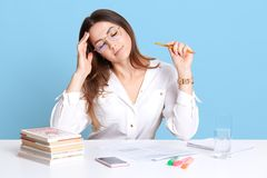 Indoor shot of exhausted young dark haired businesswoman sitting in office at white desk, keeps eyes closed, touching her forehead royalty free stock images