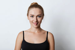 Indoor shot of funny blonde female with hair knot, showing tongue while arguing with someone, trying to persuade that she is right Stock Photo