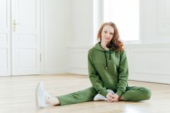 Indoor shot of glad ginger European female wears sports clothes, stretches legs on floor, wears sportshoes, has slim body, has royalty free stock photo