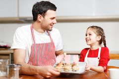 Indoor shot of handsome man wears striped apron and his small pretty female kid hold hand made cakes, rejoices stock image