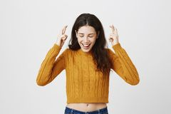 Indoor shot of happy positive caucasian woman raising hands with crossed fingers, smiling broadly while standing with. Closed eyes and lowered head over gray royalty free stock photo