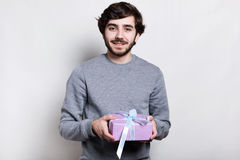 Indoor shot of happy young hipster with modern hairstyle and beard dressed in grey casual sweater holding a present in his hands g stock photos