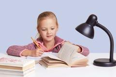Indoor shot of little blonde girl at white desk reading book or writting something, doing her homework by light of lamp, has stock photos
