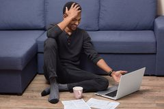 Indoor shot of overjoyed dark skinned man giggles as watches funny video on portable laptop computer, drinks coffee, surrounded royalty free stock photos