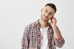 Indoor shot of pleasant good-looking man with beard in transparent glasses, rubbing ear and tilting head right, smiling. And feeling tired while standing over Royalty Free Stock Photo